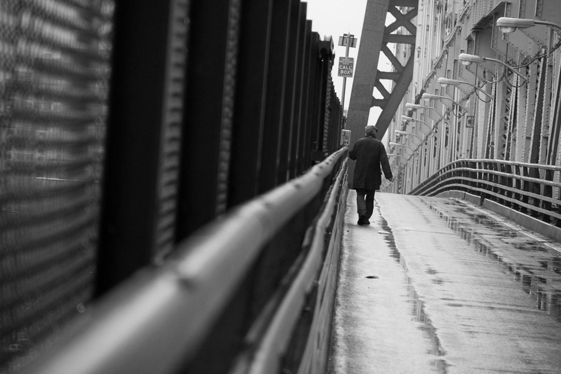Man-walking-on-bridge bw
